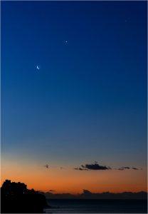 Crescent moon near 2 tiny planets in dark blue sky with a layer of orange near the dark horizon.