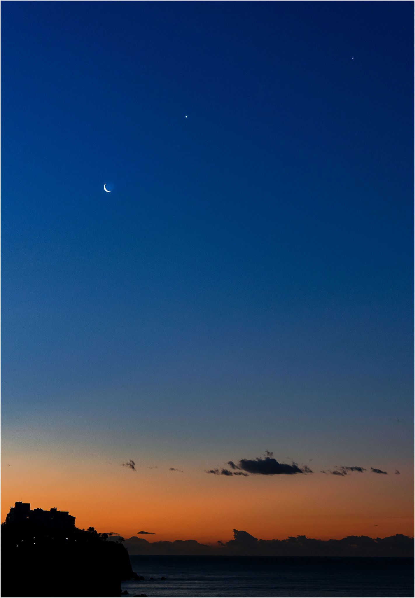 Crescent moon near 2 tiny planets in dark blue sky with a layer of orange near the dark horizon.