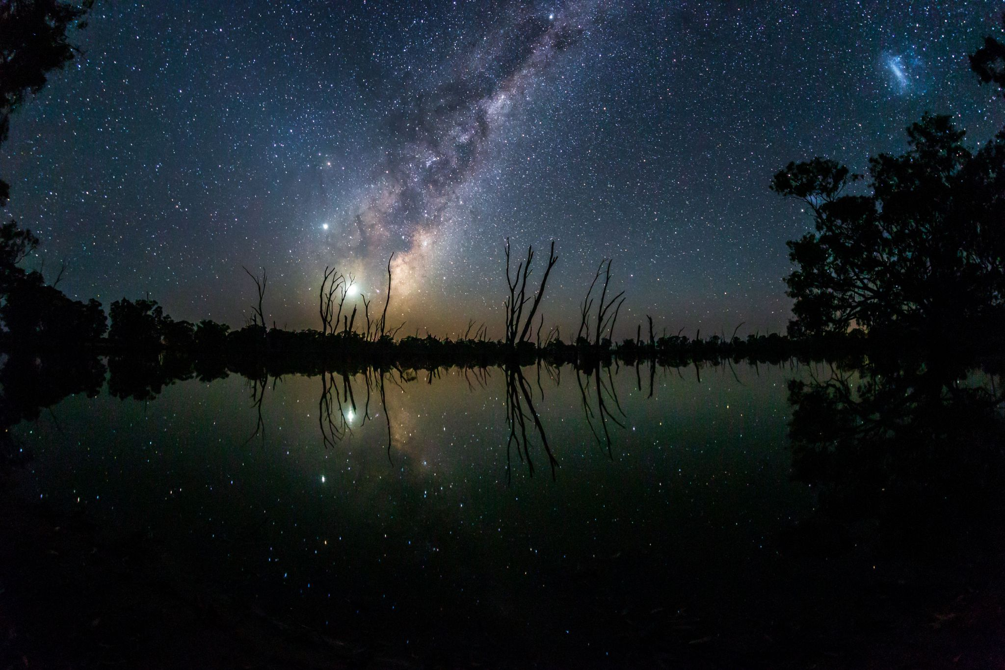 Dark blue sky with a starry band of the Milky Way, reflected in dark glassy water.