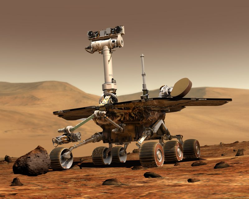 Rover: chassis on six small wheels. Solar panel wings. Cameras on pole sticking up.  Reddish landscape.