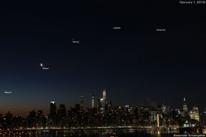 A Manhatten skyline as dawn is breaking, with the planets arced across the sky above.