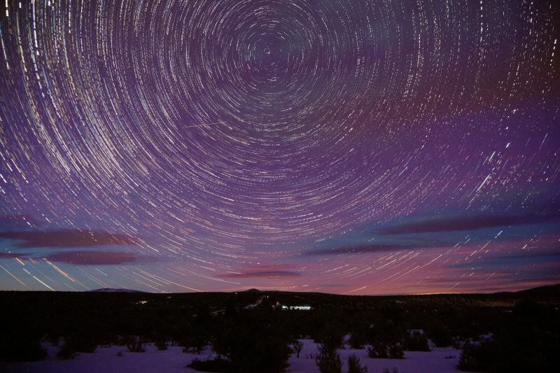 Many bright concentric circles around one star high over snowy landscape.