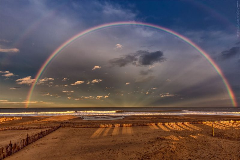 Double rainbow, anti-crepuscular rays, over a wide beach.
