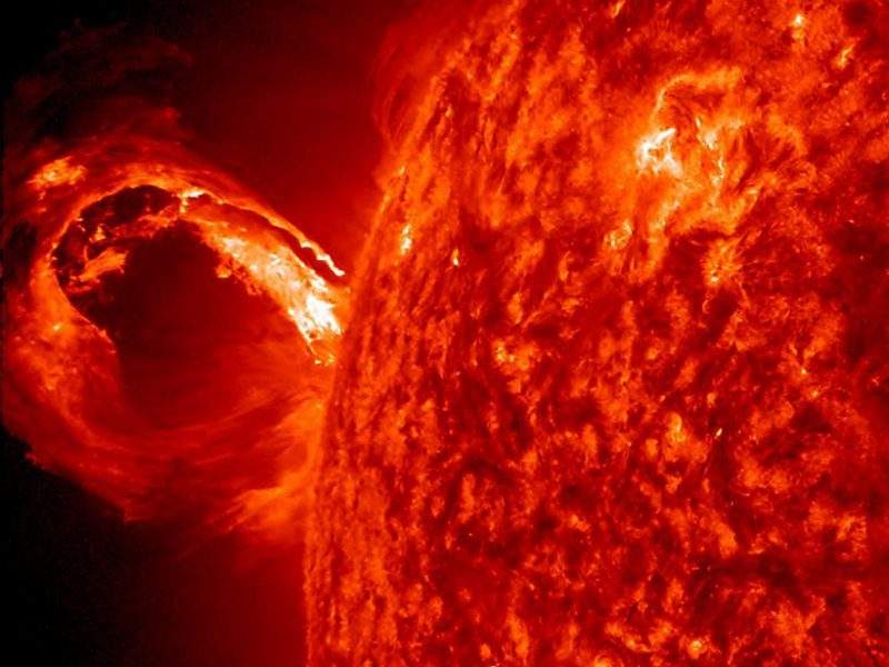 Loop of fire extending from horizon of sun.