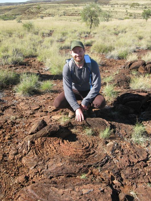 Man squatting on red-brown dirt with hand on rock composed of concentric circles.