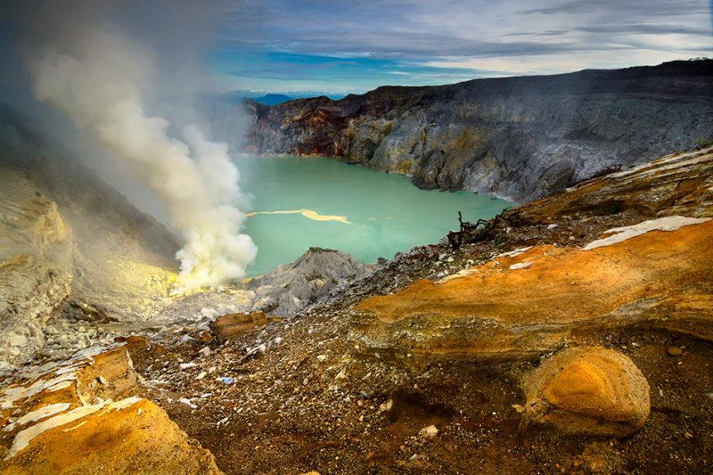 Steaming greenish lake in deep volcanic crater with yellow sulfur deposits on shore.