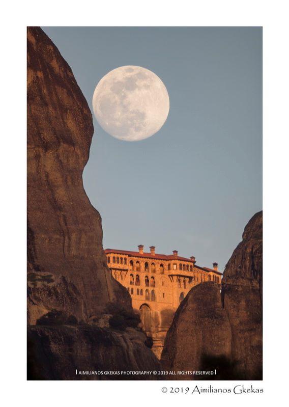 Full moon over a monastery, seen between 2 rocks