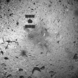 Spacecraft shadow, and a dark irregular spot, on the surface of a rocky asteroid.