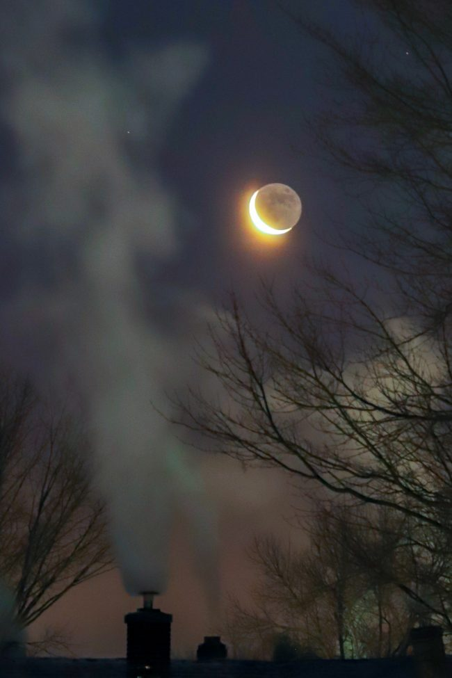 Billowing smoke from a chimney, with the moon and Venus visible to one side.
