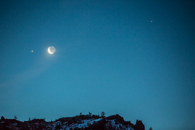 Blue twilight sky, crescent moon, a bright planet on either side of the moon, snow-covered ground below.