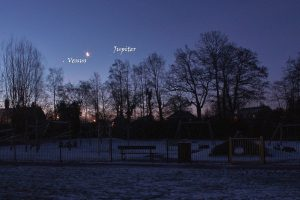 Looks like a snowy park in England, bare trees, planets and moon behind.