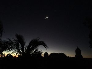 Silhouettes of tropical plants, and domed architecture, with the moon, Jupiter and Venus in the sky.