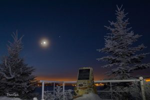Looks like an overlook, moon and planets in the sky, a handrail and icy-looking plague in the foreground.