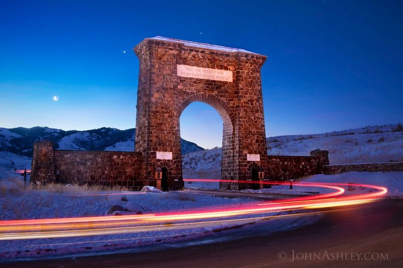 A rustic arch over a roadway, with streaks showing the movement of a car, and the planets and moon above.