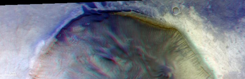 Cascading concentric dunes over edge of partial view of crater.