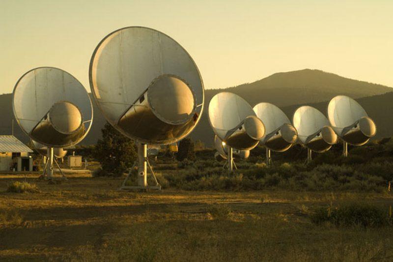 Row of 6 dish-shaped radio telescopes with large cylinders inside them.