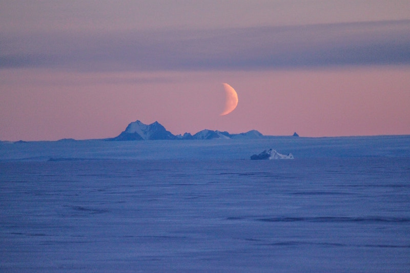 Icy landscape to a distant horizon, with ice hills and orange crescent moon above.