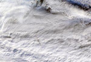 A dark streak of a meteor above bright white clouds.