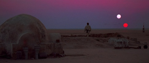 Twilight desert landscape with Luke Skywalker watching two setting suns close together.