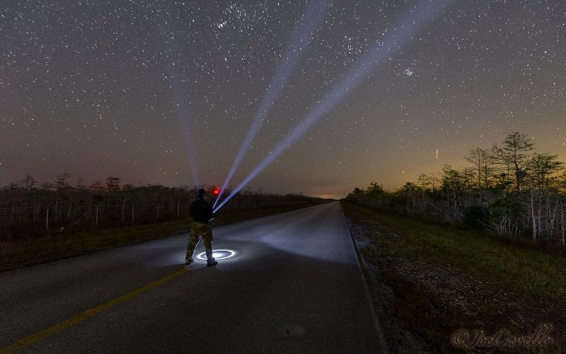 Man standing on a highway shining a flashlight into a starry sky.