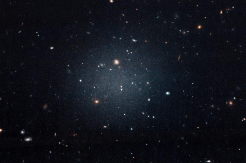 A round, fuzzy, diffuse galaxy with scattered large and small dots.