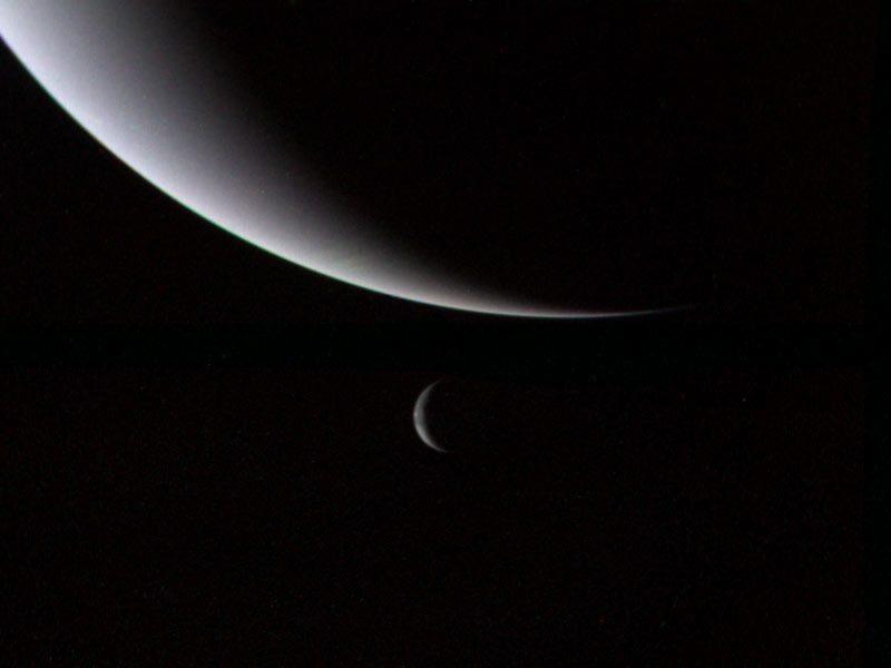 Crescent bluish large planet with crescent Triton below it.