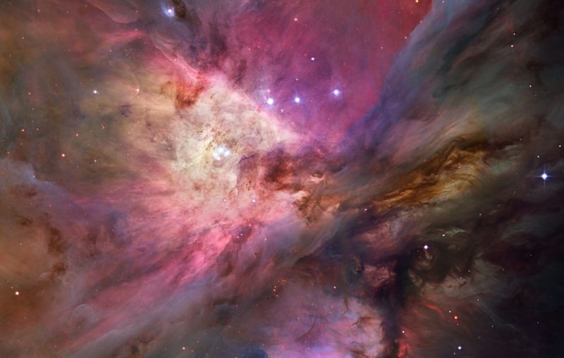 Colorful Orion Nebula cloud with scattered stars in foreground.