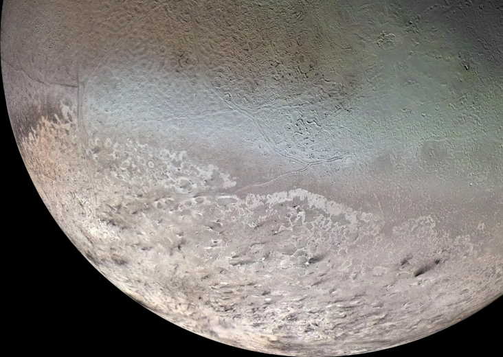Part of moon, irregular white ice at bottom, bumpy surface elsewhere.