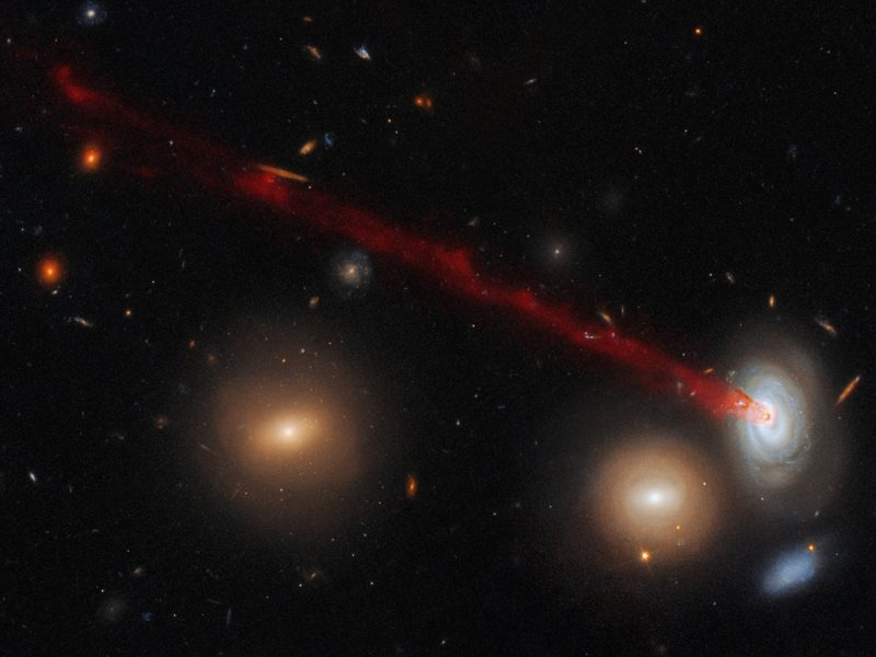 Four galaxies. Long red streak emerging from spiral galaxy.