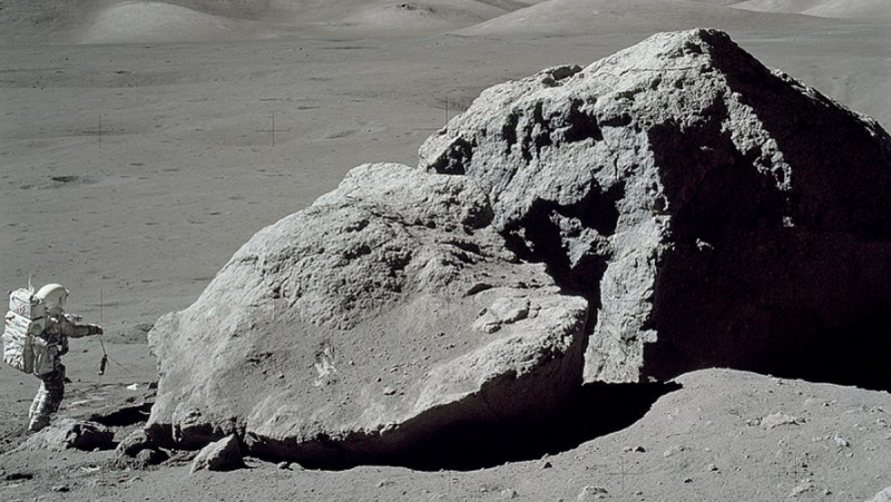 Moon-suited astronaut beside house-sized triangular boulder.