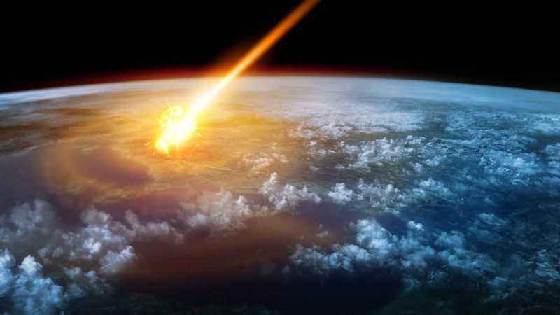 Earth from space with flaming asteroid descending through atmosphere.