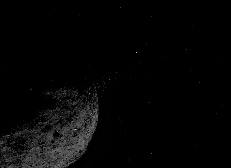 Crescent asteroid with array of tiny bright dots on one side.