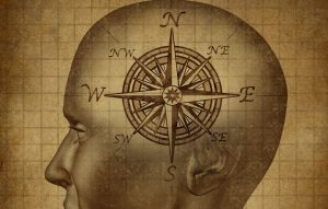 Sepia drawing of human head in profile with a compass inside.