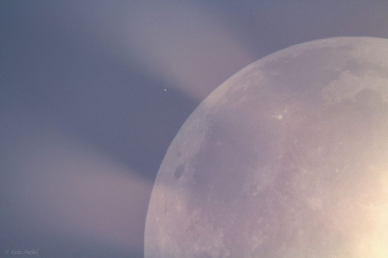 A portion of the moon, illuminated by earthshine, with what looks like crepuscular rays emanating from it.