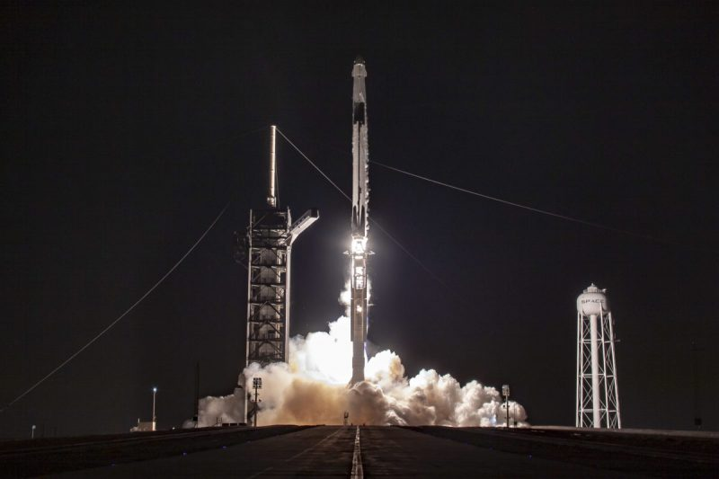 Rocket lifting off at night with clouds of white steam at the base.