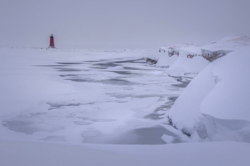 Frozen waves, lighthouse in background, icy cliffs to right.
