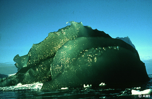 Huge brilliant green lump of ice floating in the sea, an iceberg shining in sunlight.