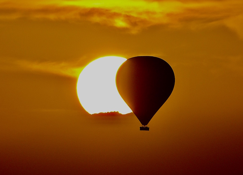 Hot air balloon in front of white sun in an orange sky.
