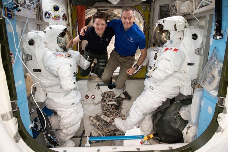 Astronauts hovering weightless in small room with large round hatch behind them