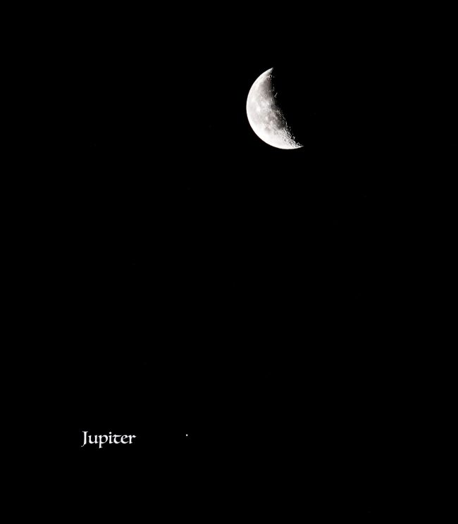 Crescent moon above a bright dot - Jupiter - against a black sky.