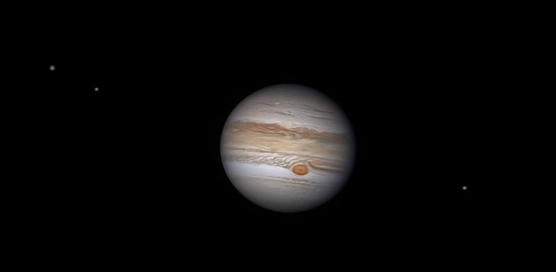 The big banded disk of Jupiter as seen through a telescope, with 3 starry points on a line with its equator.