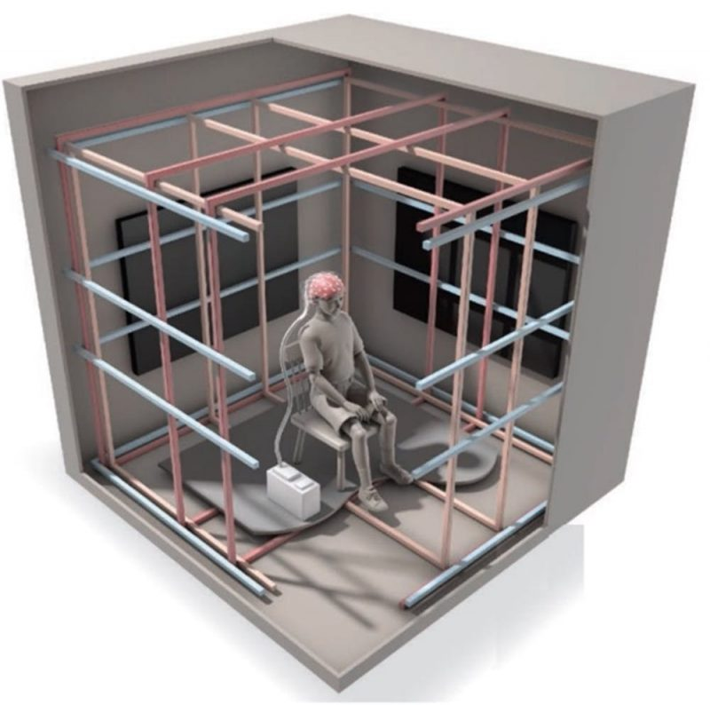 Cutaway of cage-like room with person sitting in a chair in the middle.