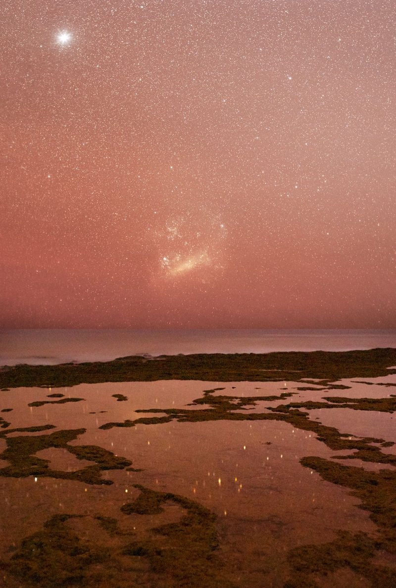 The Large Magellanic Cloud above tide pools, where stars are reflecting.
