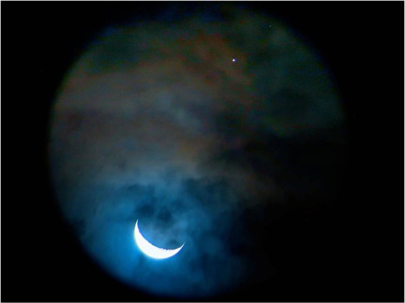 View through binoculars of the moon and Saturn.