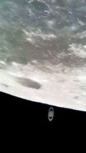 A telescopic view of the moon and Saturn, with Saturn right next to the moon.
