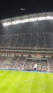 View from inside a brightly lit stadium full of people with very thin crescent moon above.