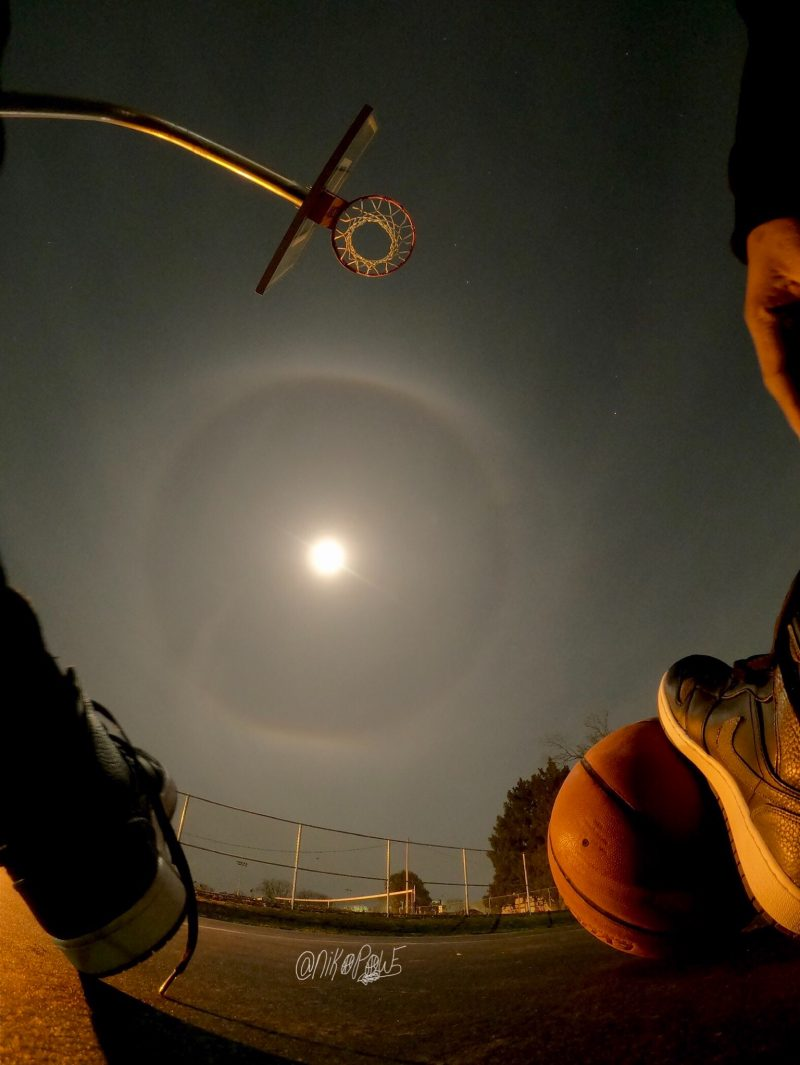 View straight up through basketball hoop with moon to one side with wide halo around it.