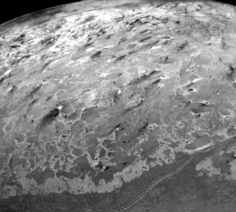 Dark streaks coming from bright dots - geysers on Triton.