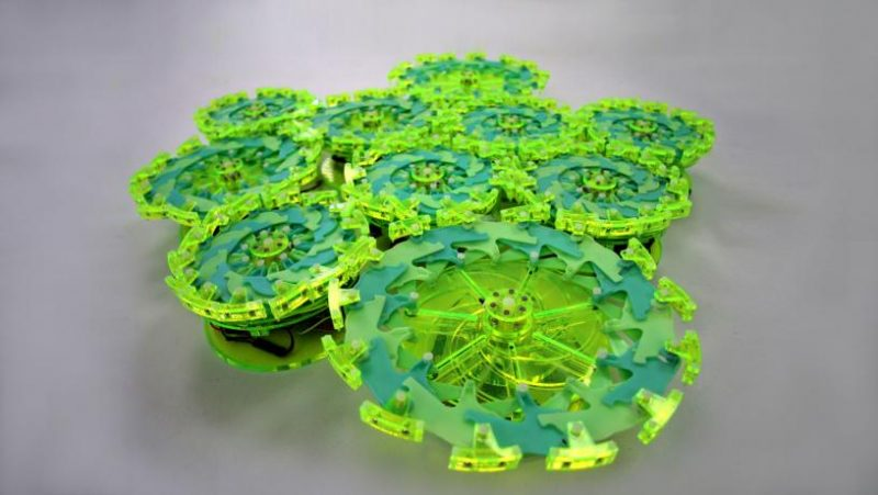 10 circular disks with tiny arms around the edges, machinery in center.