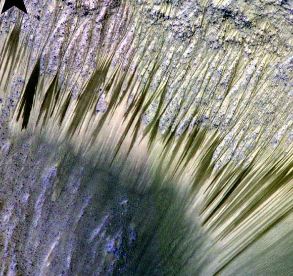 Long, thin dark streaks on the walls of a crater.